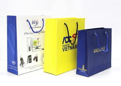 Бумажные пакеты с лого типом. Белый бумажный пакет с плоским дном, желтый бумажный пакет, синий бумажный пакет с золотым тиснением надписи